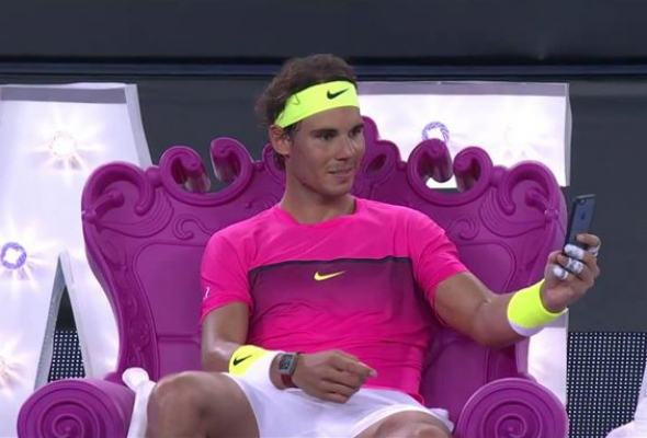 Rafael Nadal seated on Queen of Love chair checking his phone